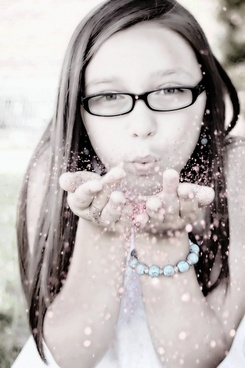 girl blowing glitter face portrait