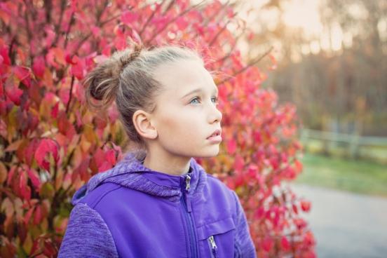 cute girl in blue coat by red leaves
