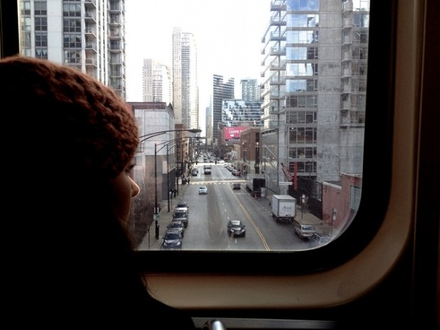 girl in beanie hat peering at downtown city on train