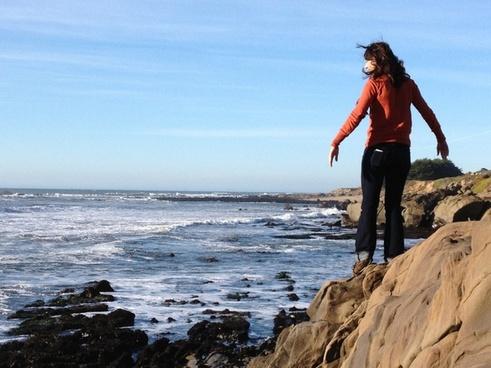 girl standing on rocks on ocean coast