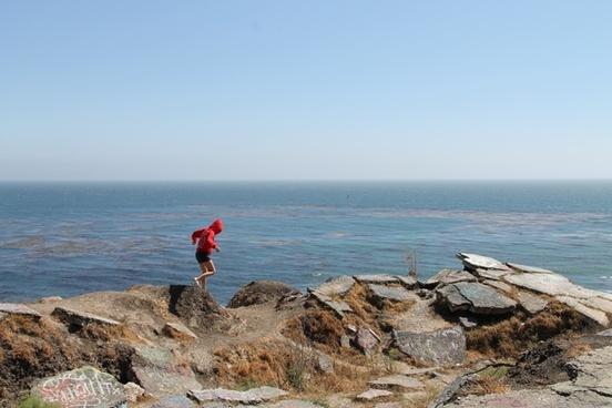 girl walking across rocks by ocean
