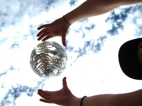hands over suspended silver ball