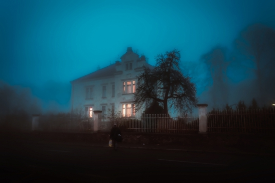 man in front of house covered by fog