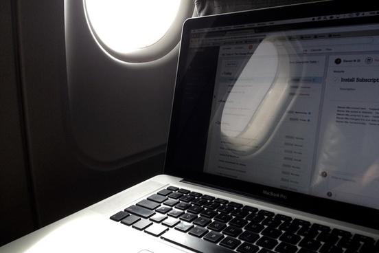 laptop next to airplane window