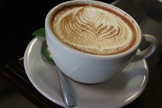 leaf latte art in a white mug on a dish