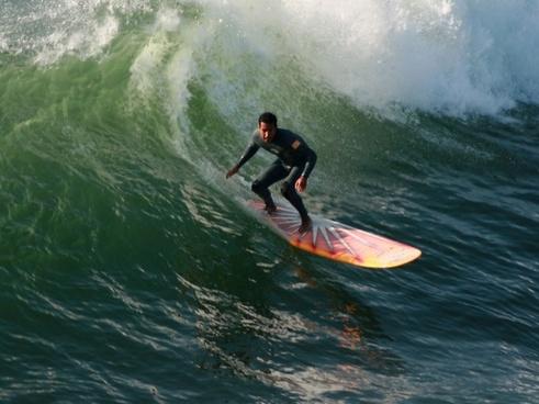 longboard surfer drops in on a wave