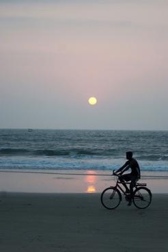 man bicycle beach