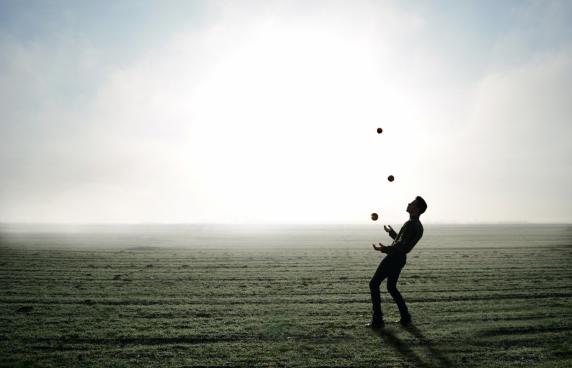 man juggling balls
