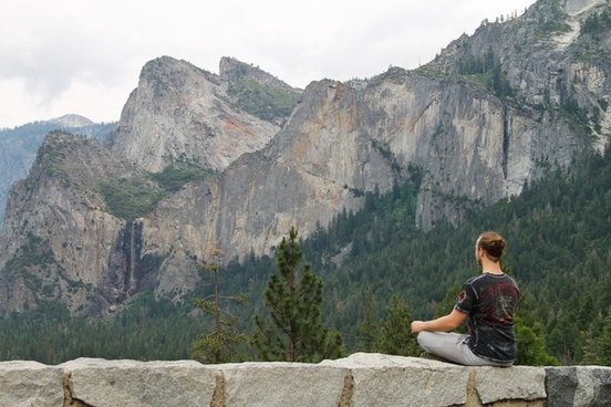 man meditating by mountains