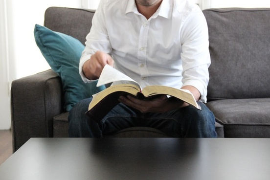 man on couch turning page of bible