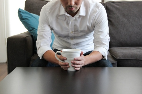 man on couch with coffee mug