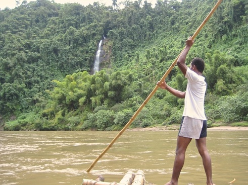man on raft in a river through the jungle