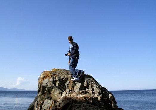 man on top of rocky boulder