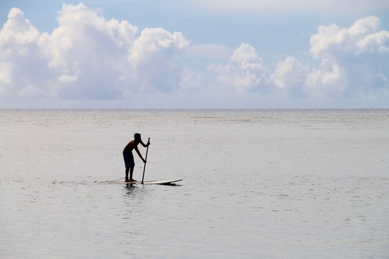 man paddling on surfboard in ocean