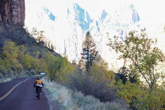 man riding on bicycle alongside mountains