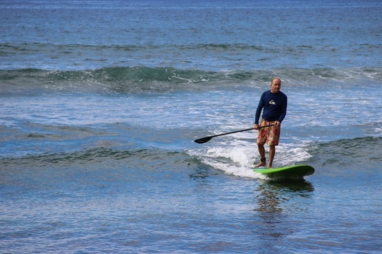 man riding paddle board in ocean