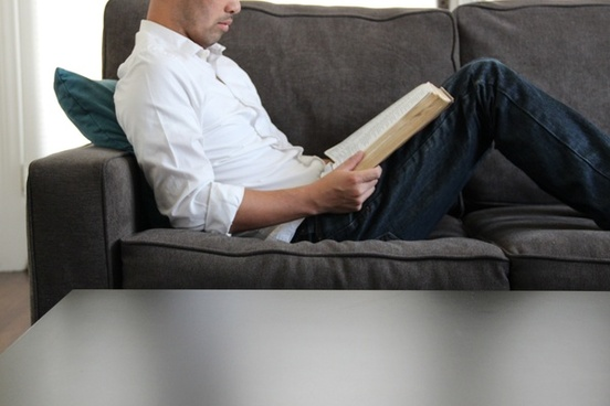 man sitting on couch reading bible