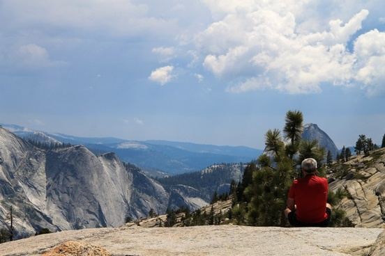man sitting on rock looking at scenic view