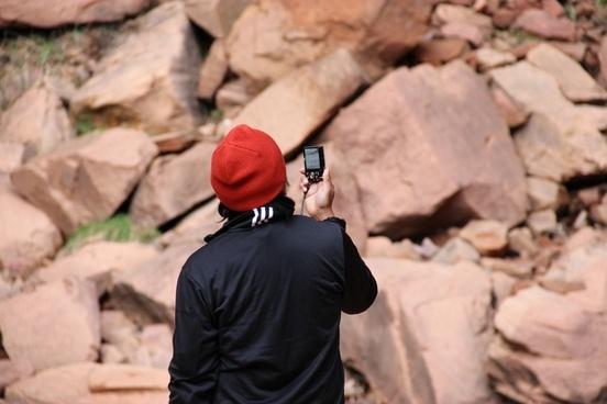 man taking photos of rocks