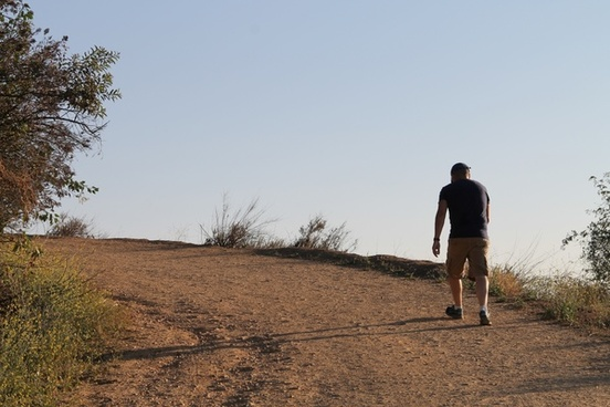 man walking up a dirt trail