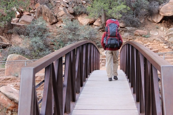 man with hiking backpack walking across bridge
