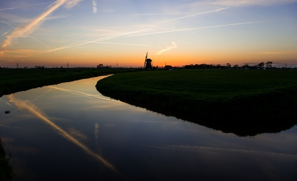 mill at sunset with a river in front