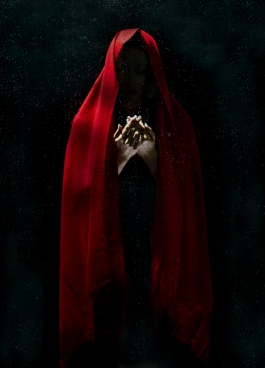 magical human in dark with red head covering