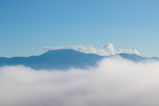 mountains rising above clouds
