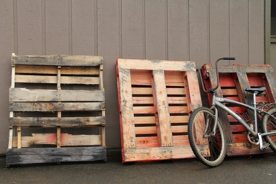 old bicycle leaning against wood pallets