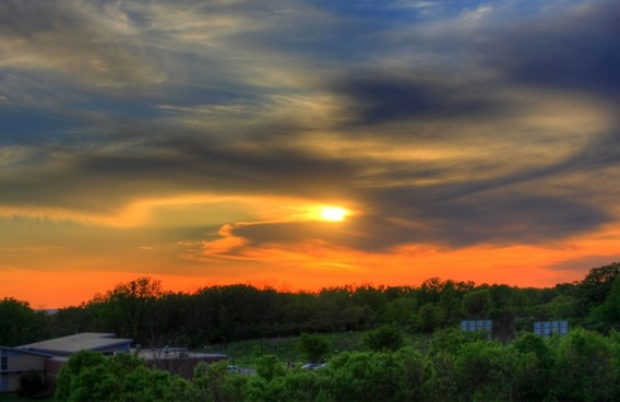 orange sunset behind clouds in the distance in southern wisconsin