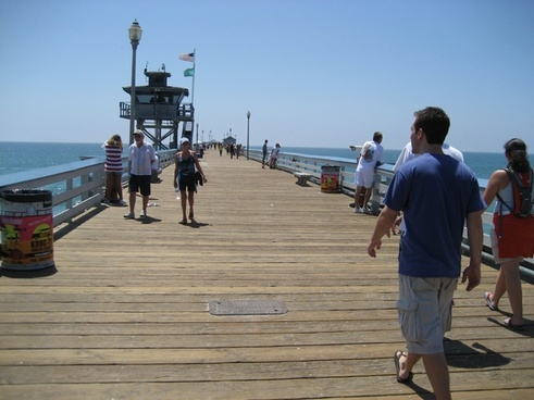 people walking along ocean pier