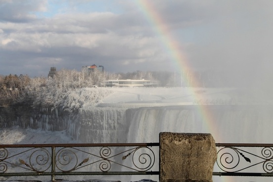railing in front of rainbow over frozen niagara falls