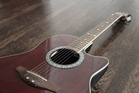 red acoustic guitar angled on wood floor
