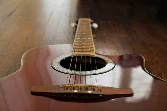 red acoustic guitar on wood floor