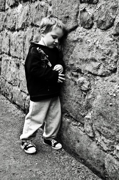 sad child at a stone wall
