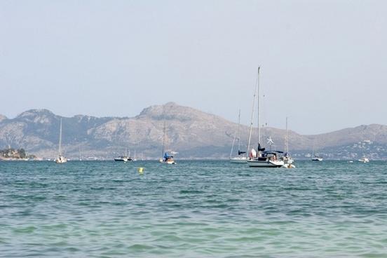 sailboats idling in mediterranean bay