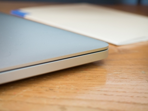 side of laptop on desk with white book
