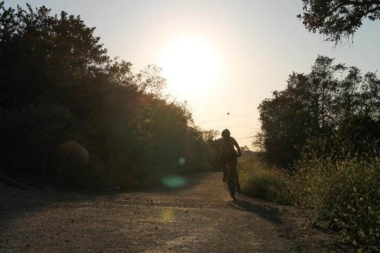 silhouette of bike rider on dirt path