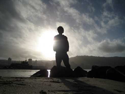 silhouette of man standing on beach against city