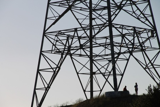 silhouette of people under electric tower