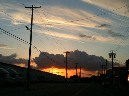 silhouette of telephone poles against cloudy sunset
