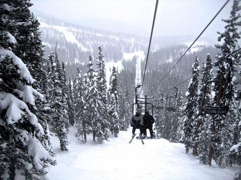 ski lift going up snow covered mountain
