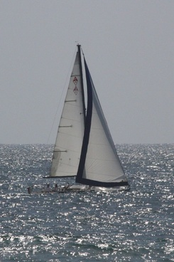 small sloop riding low in the water