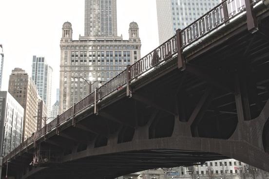 steel bridge in front of tall buildings in city