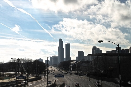street going into downtown city with clouds in sky