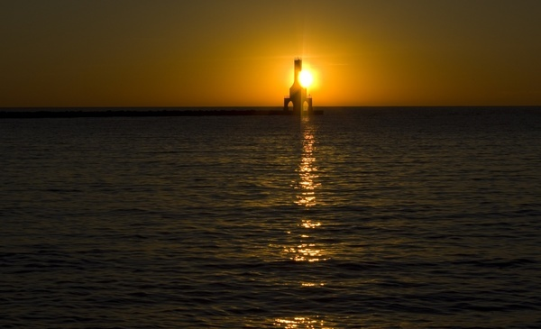 sun behind the lighthouse at port washington wisconsin