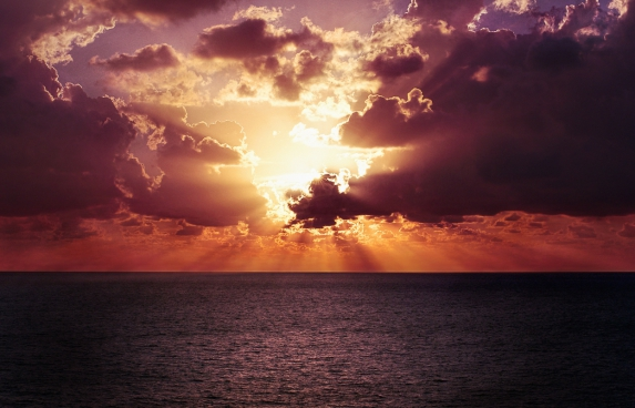 sun rays shining through clouds during calm ocean sunset
