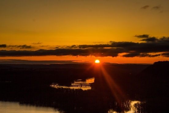 sun rising over the landscape of the mississippi river at pikes peak state park iowa