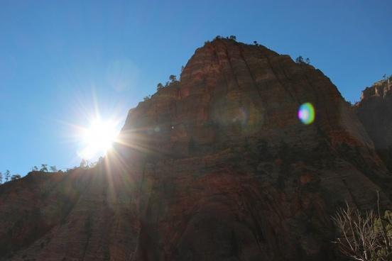 sun shining next to rock mountain