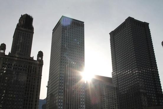 sun shining through 3 skyscraper buildings